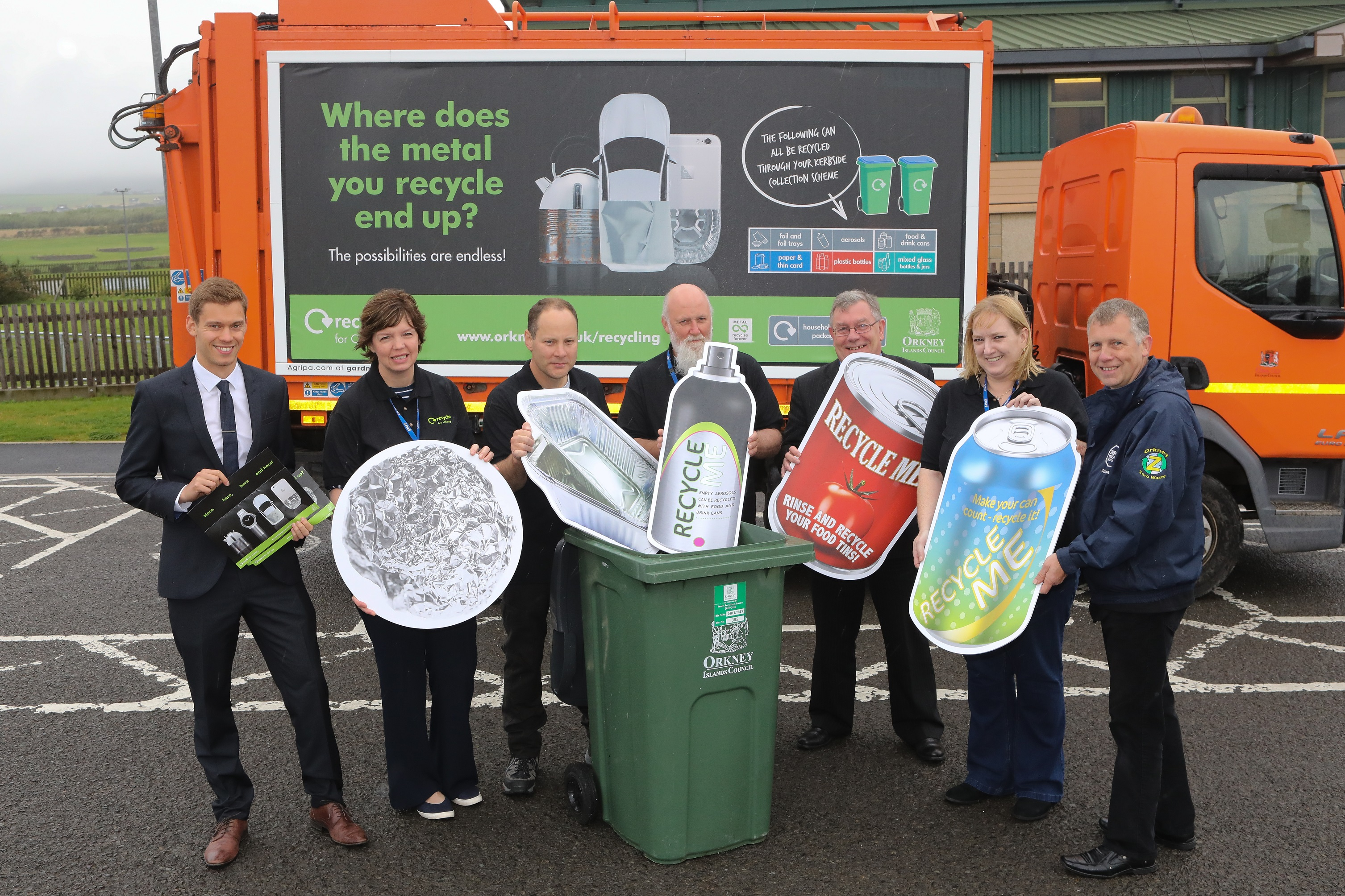 A group of representatives from MetalMatters and Orkney Council holding cardboard cut-outs of metal packaging items in front of one of their recycling vehicles which bears the MetalMatters signage artwork.